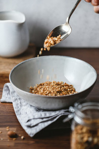 Hand sprinkles baked granola in a ceramic bowl  Healthy vegetarian breakfast