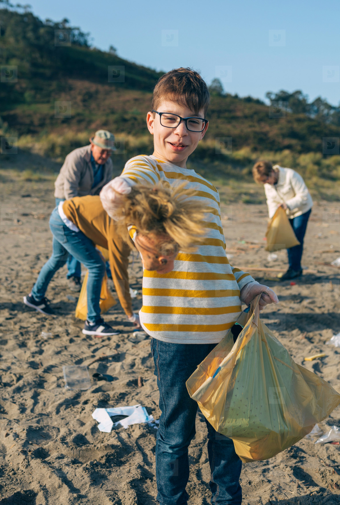 Boy showing doll head while cleaning the beach