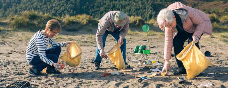 Senior volunteers cleaning the beach