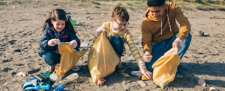 Young volunteers cleaning the beach