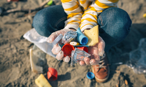 Child hands with garbage from the beach