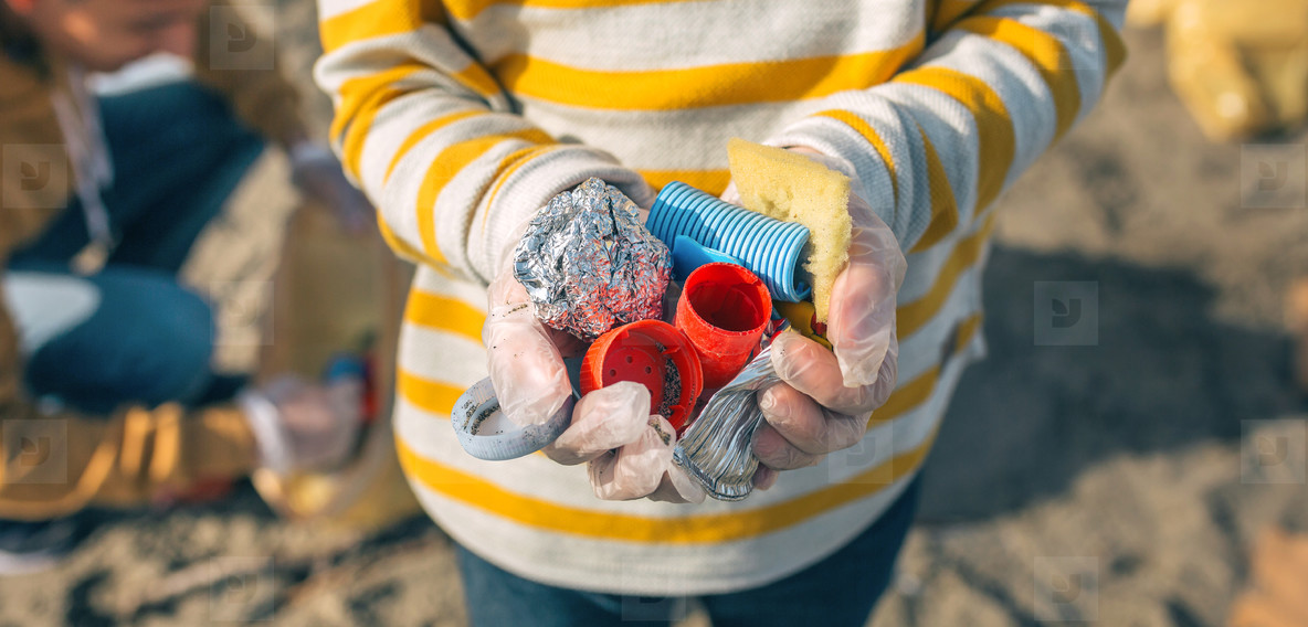 Boy hands with garbage from the beach