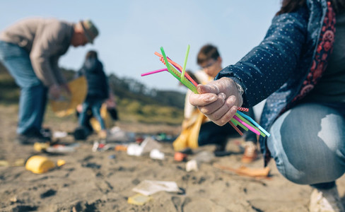 Woman showing handful of straws collected on the beach