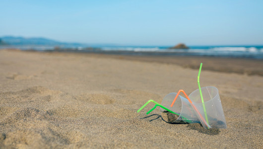 Beach with plastic cups and straws