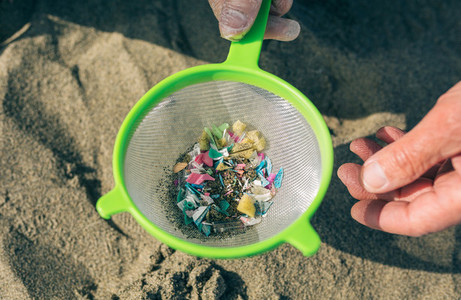 Colander with microplastics on the beach