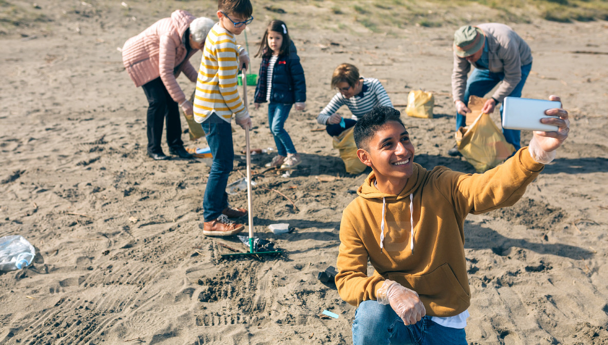 Young man taking selfie to group of volunteers cleaning beach