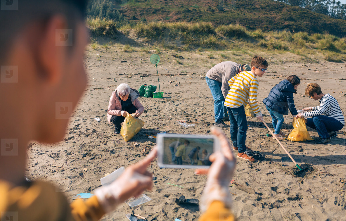 Young man taking photo to group of volunteers cleaning beach