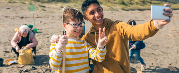 Young man and boy taking selfie to group of volunteers cleaning beach