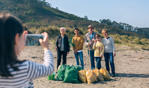 Girl taking photo to group of volunteers after cleaning beach
