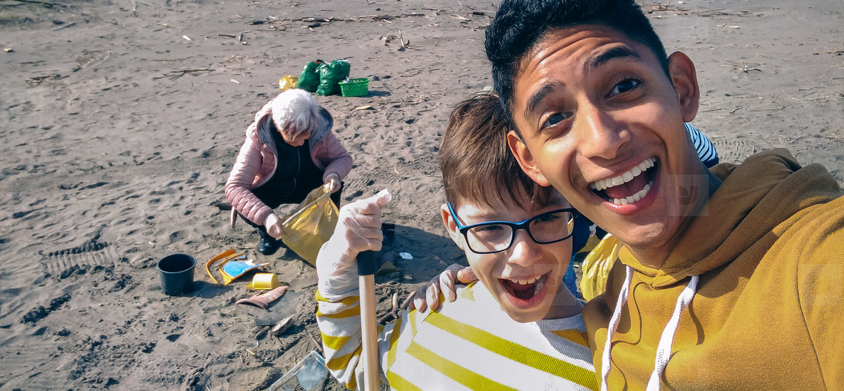 Young man and boy taking selfie while group of volunteers cleaning beach