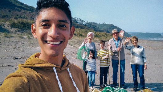 Young man taking selfie to group of volunteers after cleaning beach