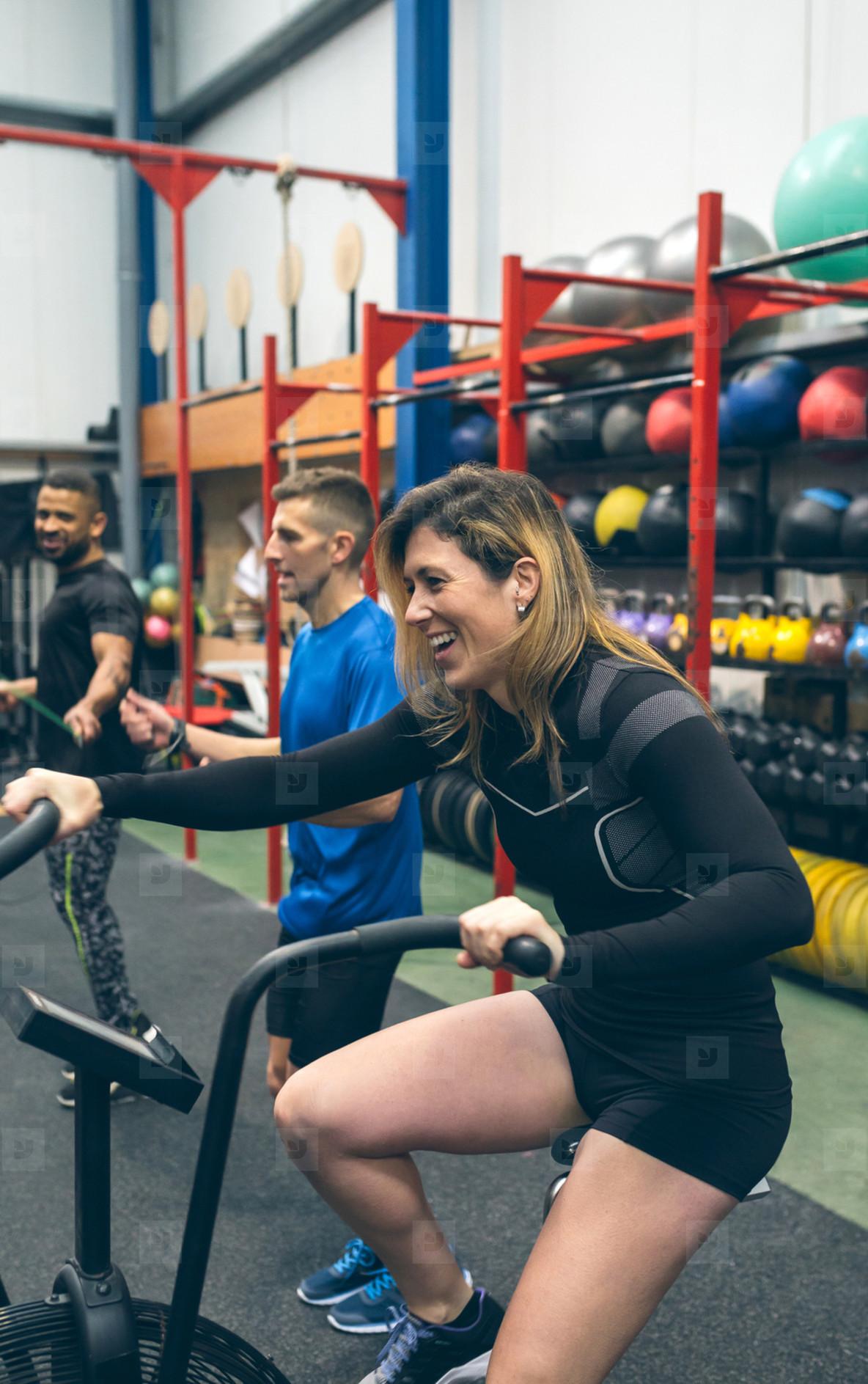 Sportswoman doing air bike at the gym
