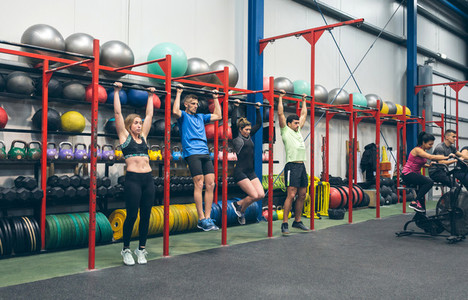 Athletes doing pull ups in the gym