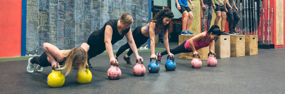 Sportswomen training with kettlebells and sportsmen doing box jumps