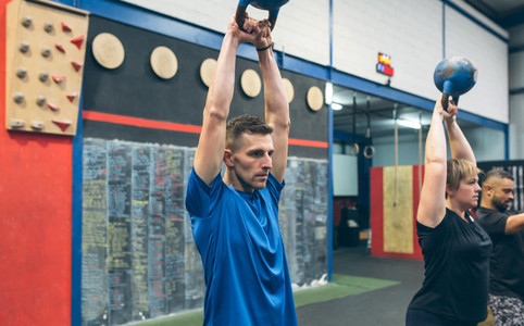 Sportsman exercising with kettlebell with his partners