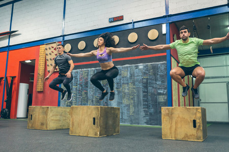 Athletes exercising jumping wooden box