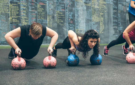 Sportswomen doing push ups with kettlebells