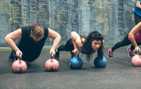Sportswomen doing push ups with kettlebells