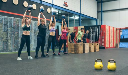 Sportswomen with kettlebells and sportsmen in background
