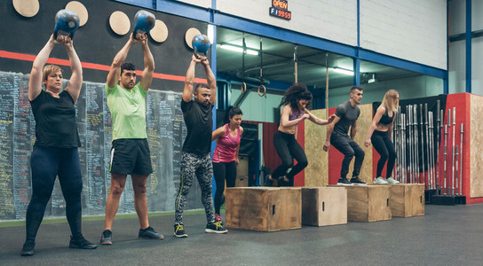 Athletes exercising with kettlebells and doing box jumps