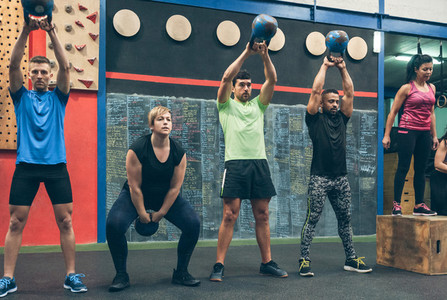 Athletes exercising with kettlebells indoors