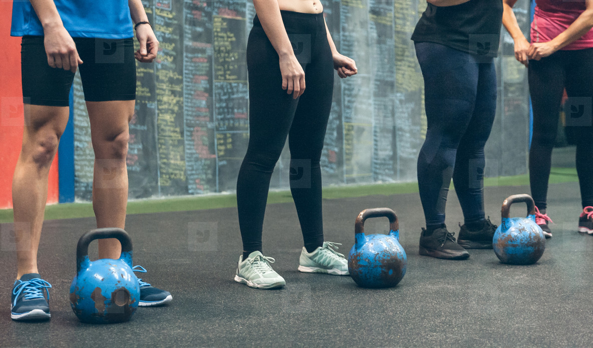 Unrecognizable group of athletes with kettlebells