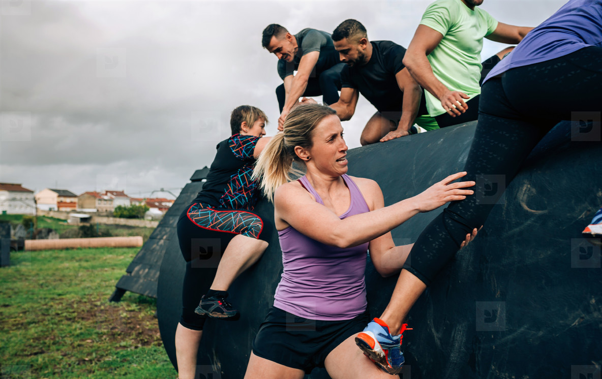 Participants in an obstacle course climbing a drum