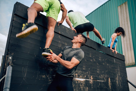 Participants in obstacle course climbing wall