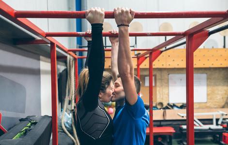 Athletes kissing exercising on monkey bars