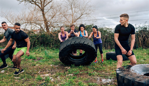 Female participants in an obstacle course turning a wheel