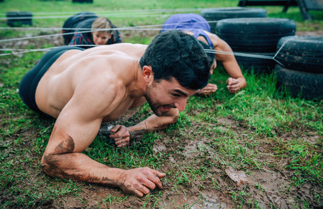 Male participant in an obstacle course crawling