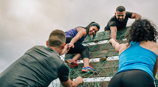 Participants in obstacle course climbing net