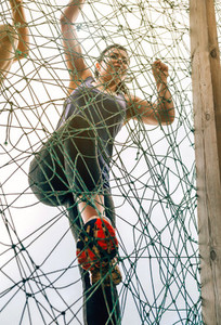 Participant in obstacle course climbing net