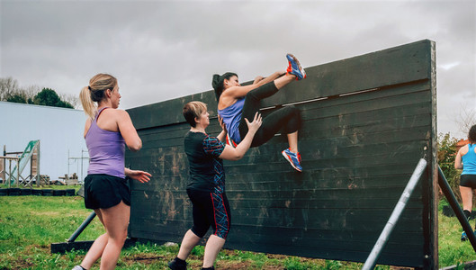 Female participants in obstacle course climbing wall