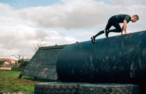 Man in an obstacle course climbing a drum