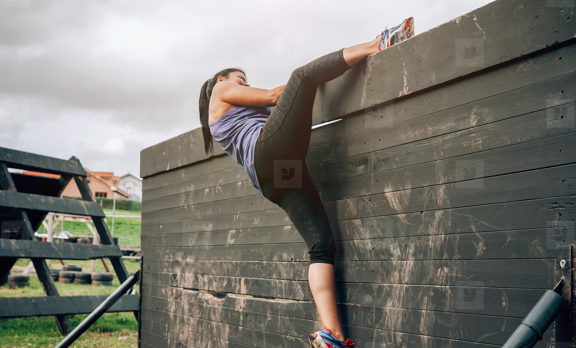 Participant in obstacle course climbing wall