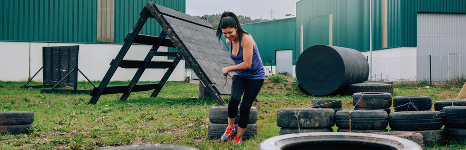 Participant in an obstacle course dragging wheels