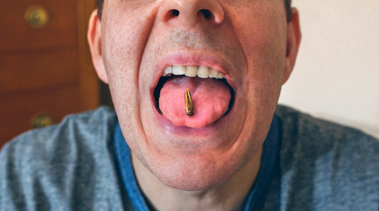 Man showing a cricket on his tongue