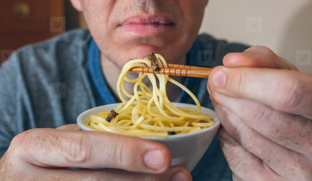 Unrecognizable man eating spaghetti with crickets