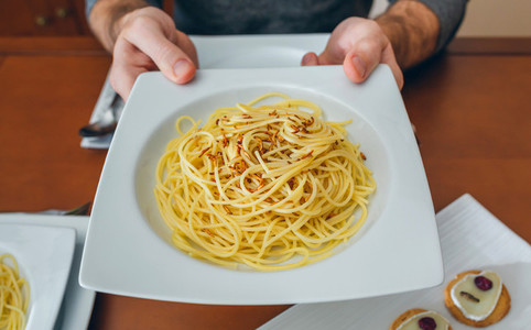 Hands of man showing spaghetti with worms dish
