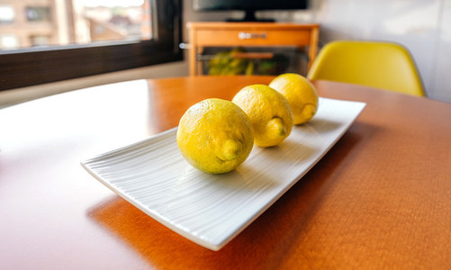 Three lemons on a white plate