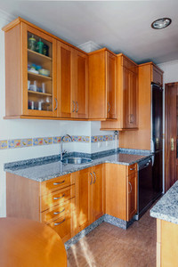 Kitchen with wooden furniture and stainless steel appliances