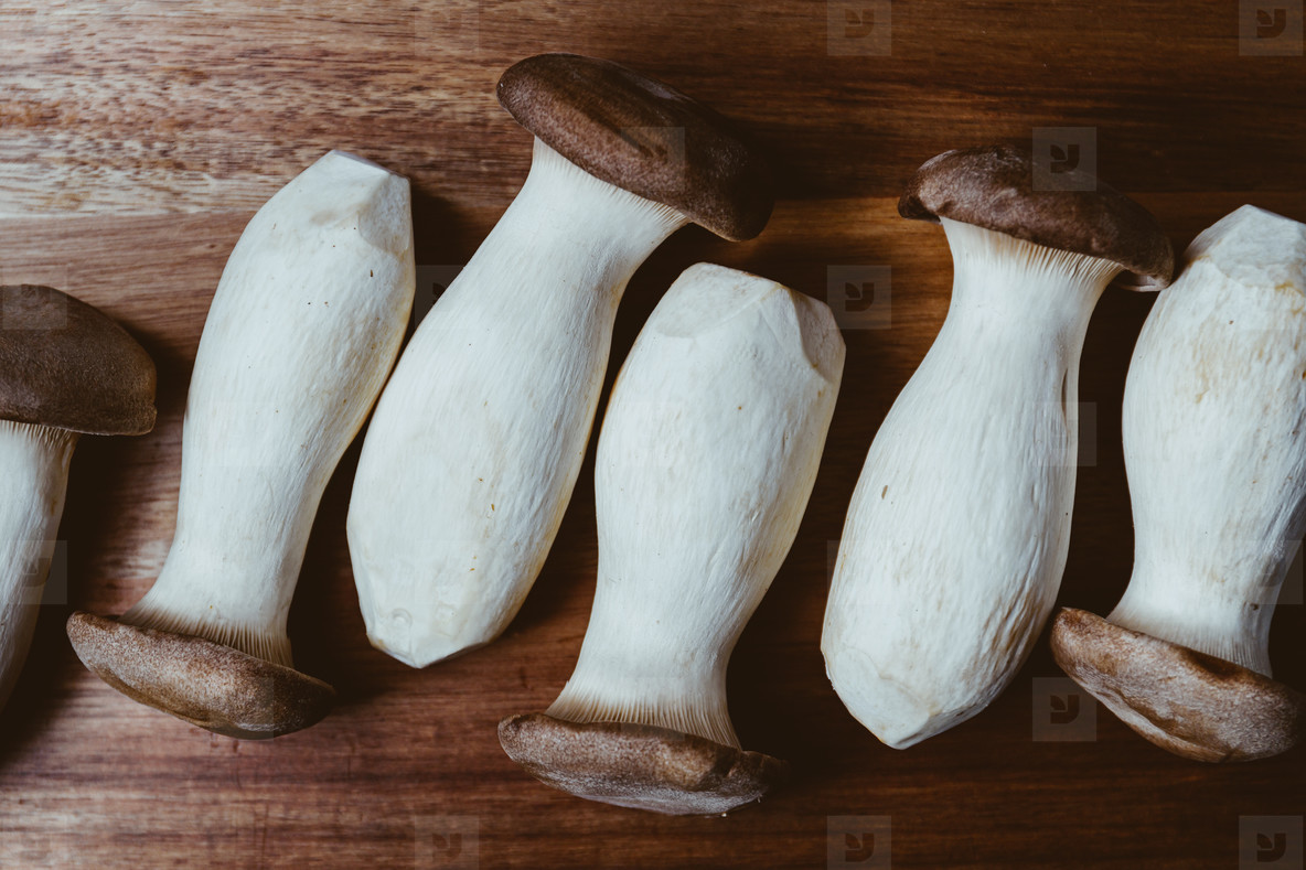 Group of raw King Oyster mushroom also known as eryngii on a wooden cutting kitchen board  Top view