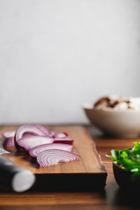Close up of wooden cutting board knife and onion on a kitchen table Cooking concept
