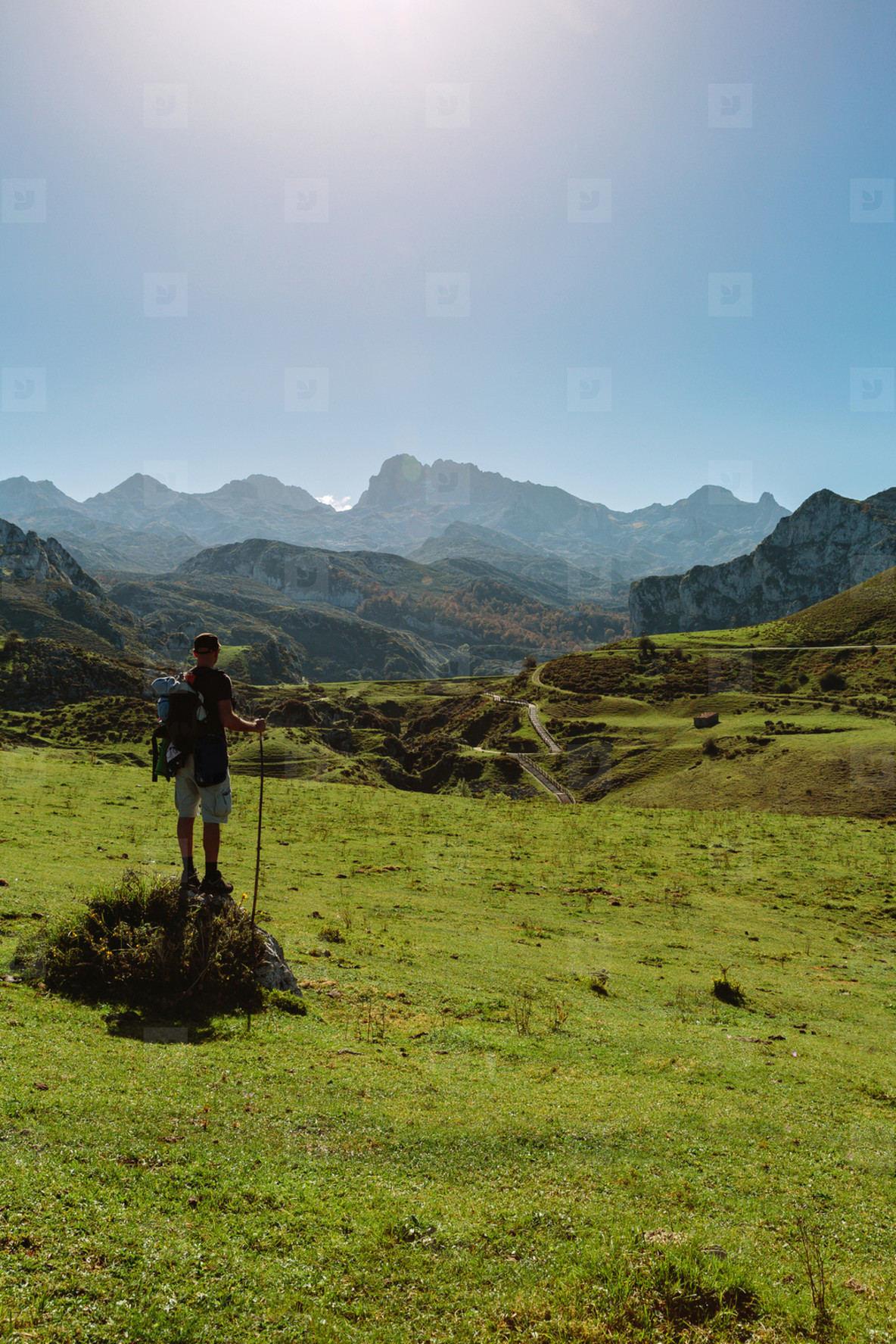 Mountaineer looking landscape with path between mountains