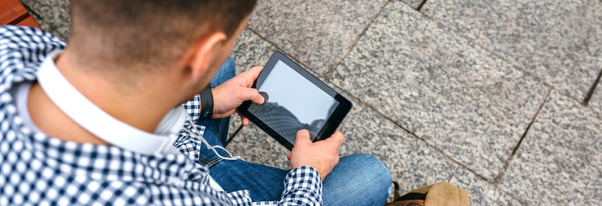Unrecognizable young man using tablet