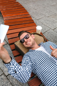 Man lying on a park bench making selfie with mobile