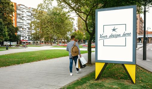 Man walking beside a customizable advertising poster