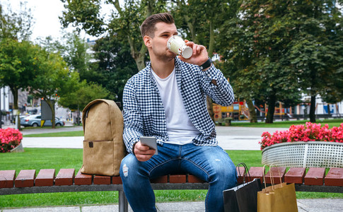 Man with mobile drinking coffee sitting on a bench