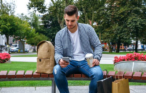 Man looking mobile sitting on a bench